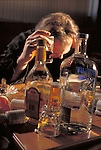 depressed man drinking alcohol, surrounded by empty bottles and drugs