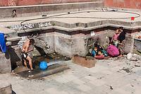 Nepal, Patan.  Public Fountain.  Women Getting Drinking Water on right, Man Bathing on left.