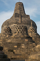 Borobudur, Java, Indonesia.  Approaching the Topmost Stupa.  The diamond-shaped holes symbolize the passions that still linger as men rise toward Nirvana.  The top two, with square-shaped openings, symbolize the overcoming of passions as one approaches Nirvana.