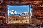 The Teton Mountain Range can be seen through the window of the old, historic Cunningham Cabin.