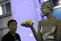 A model holds a Geely Meirenbao model at the Auto China 2004 exhibition in Beijing June 12, 2004. The private carmaker in Zhejiang province aims to double its sales to 165,000 cars this year by producing the low-cost Geely Haoqing, Merrie, Ulion, Meirenbao and Maple cars.(Lou Linwei/Sinopix)