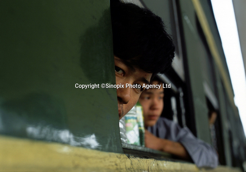 A young man  looks out from the window of a train from Dazhou, Sichuan province to Guangzhou at the railway station of Dazhou, Sichuan province, China..22-OCT-03
