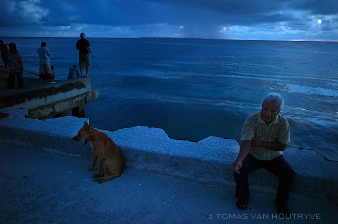 Residents wait at the wharf or fish in the evening no Ebeye, Marshall Islands on June 21, 2012. Due to the lack of a functioning sewer system, much of the water around Ebeye is contaminated.