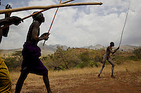Bugu's group advances to the rival group in another village where Bugu has a dispute with another young tribesman over a woman.  They sing as they walk and carry their fighting sticks that are carved in the shapes of penises.