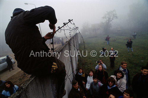Lichterfelde, Berlin (West) and Teltow, Potsdam (East) crossing post, Germany<br /> November 14, 1989 <br /> <br /> People watch as Germans cut wires to open the Berlin Wall. Germans gathered as the wall is dismantled and the East German government lifts travel and emigration restrictions to the West on November 9, 1989.