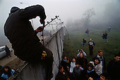Ostpreu Bendamm, Germany<br /> November 14, 1989 <br /> <br /> People watch as Germans cut wires to open the Berlin Wall. Germans gathered as the wall is dismantled and the East German government lifts travel and emigration restrictions to the West on November 9, 1989.