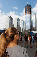 A woman looks at the rising Freedom Tower (One World Trade Center), while standing on Greenwich Street across from the entrance to the National September 11 Memorial.
