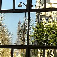 On the mirror glasses of a definitely geometrically divided window, the reflected image of the Eiffel tower and of a characteristic Parisian building, with a street lamp and bare and green trees (Paris, 2007).<br /> <br /> Sui vetri a specchio di una finestra nettamente divisa geometricamente, l'immagine riflessa della torre Eiffel e di un caratteristico edificio Parigino, con un lampione e alberi spogli e verdi (Parigi, 2007).