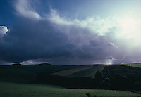 Sunlight streaming through clouds over fields<br />