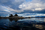 Islet in Blackfish Sound area shimmers in evening light as a storm passes, near Stubbs Island, Broughton Strait, and Telegraph Cove on Vancouver Island, Canada. Kayak camp site.