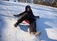 Gabe Newton, 9, of Prairie Grove slows himself with his feet Friday, Feb. 19, 2021, as he slides downhill on a storage container lid while sledding with his family at Battlefield State Park in Prairie Grove. The Newtons were taking a break from virtual instruction to take advantage of the good sledding conditions before warm temperatures melted the snow from the hillside. Visit nwaonline.com/210220Daily/ for today's photo gallery. <br /> (NWA Democrat-Gazette/Andy Shupe)