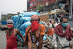Daily wage laborers covers their face with mask and cloth to avoid covid 19 virus at burrabazzar in Kolkata.   Whole sale market reopened in Kolkata few days back midst 21 days lock down in India due to covid 19 pandemic. Kolkata, West Bengal, India. Arindam Mukherjee.