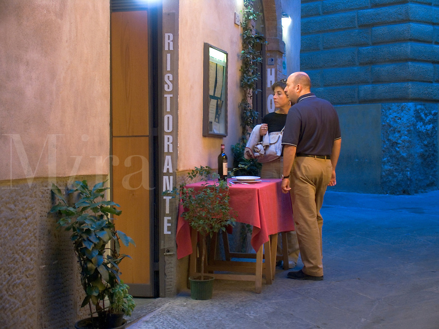 Couple reading menu outside restaurant, Siena, Ital