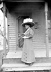 """MAMIE GRIFFIN AT 915 U STREET, 1914. The house number 915 is clearly visible above the plumed hat of this well-dressed matron. The close-up view displays the lace detailing of her dress and the title of her book, The Wife of Monte Cristo. The book was a sequel (by a different author) to the immensely popular The Count of Monte Cristo by Alexandre Dumas.<br /> <br /> ADDITIONAL INFORMATION SUBMITTED BY DELEON TODD 2/22/2017: Mamie L. Griffin (wife of Edward J. Griffin) was born in 1895. According to the 1913 Lincoln City Directory, she & husband lived @ 642 N. 9th St. The 1930 U.S. Census lists Mamie as """"Mayme"""" & the couple's address was then 2225 S. St. (Ward 8). They owned their own home. Edward (1883-1939) was a cook & railway porter. Mamie/Mayme was a homemaker. I found Mr. Griffin's grave location @ Findagrave.com. I can only assume Mamie was buried at the same location, but I haven't been able to thus far find any data confirming her death date or burial location.<br /> <br /> Ed Zimmer 2/22/2017: She sold the S St. house to Melvin Shakespeare in 1941 and that's where I lose track of her.<br /> <br /> <br /> Photographs taken on black and white glass negatives by African American photographer(s) John Johnson and Earl McWilliams from 1910 to 1925 in Lincoln, Nebraska. Douglas Keister has 280 5x7 glass negatives taken by these photographers. Larger scans available on request."""