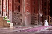 Agra, India.  Taj Mahal Mosque Interior.  Imam Reading the Koran while awaiting Prayer Time.  The steps of the minbar, from which the imam gives his sermon, are on the left.