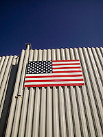 Steel American flag bolted to side of steel fence<br />