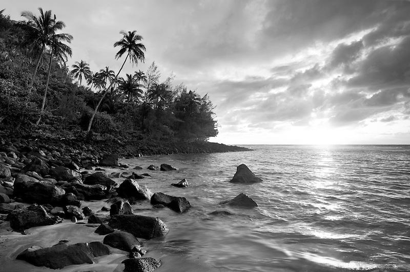 Sunset at Kee Beach with palm trees. Kauai, Hawaii.
