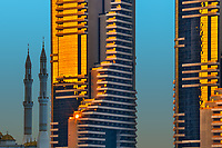 Last sunset sunrays reflecting on modern skyscraper buildings, in contrast with the mosque's beautiful minarets, in Dubai, United Arab Emirates, Asia