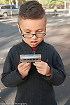 5 year old boy looking at favorite train car, outside in playground, special needs, autism spectrum