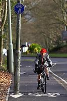 Josh  riding Islabike  bicycle on shared pavement / cyclepath in Hall Grove School uniform with school backpack ..Virginia Water , Surrey   February 2008..