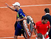 28-05-10, Tennis, France, Paris, Roland Garros, Thiemo de Bakker wuift met een verbeten gezicht naar het publiek,  Jo-Wilfriet Tsonga pakt zijn tas in