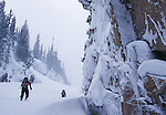 men xx skiing below Loch Vale in the backcountry of Colorado in Rocky Mountain National Park during a winter storm