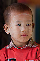Myanmar, Burma.  Little Burmese Boy of Pre-School Age, Intha Ethnic Group, Inle Lake, Shan State.  He has thanaka paste on his face, a cosmetic sunscreen.