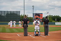 Florida Fire Frogs catcher Zack Soria, flanked by umpires Dillon Wilson (left) and Ben Fernandez (right) during the national anthem before a Florida State League game against the Jupiter Hammerheads on April 8, 2019 at Osceola County Stadium in Kissimmee, Florida.  Florida defeated Jupiter 7-6 in ten innings.  (Mike Janes/Four Seam Images)