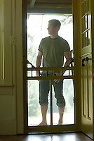 Young man standing on porch viewed through screen door