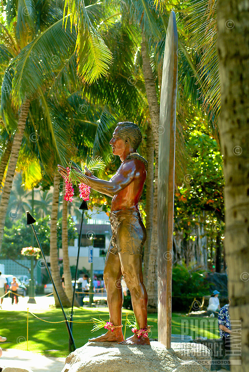 Statue of surfer standing against an upright surfboard amid palm trees at Queens Surf Beach.