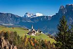 Italy, Alto Adige - Trentino (South Tyrol), Renon: view across the earth pyramides (Hoodoos), village Monte di Mezzo with church St. Nikolaus (built 1200) towards the Dolomites with Sassolungo (Langkofel), Sasso Piatto (Plattkofel) and Sciliar (Schlern) mountains | Italien, Suedtirol (Alto Adige-Trentino), Ritten: Blick ueber die Erdpyramiden und Mittelberg am Ritten mit der St. Nikolauskirche (erbaut um 1200) in die Dolomiten mit Langkofel, Plattkofel und dem Schlern (rechts)