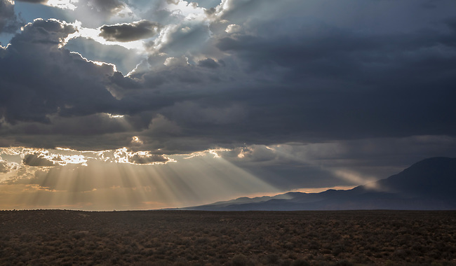 Stormy skies pass through the Southern Utah landscape and produce sunbeams at sunset