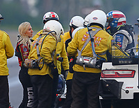 Jun 2, 2018; Joliet, IL, USA; NHRA funny car driver John Force (right) is helped from his car by the Safety Safari safety team after crashing into the wall as daughter Courtney Force (left) looks on during qualifying for the Route 66 Nationals at Route 66 Raceway. Force would walk away from the crash. Mandatory Credit: Mark J. Rebilas-USA TODAY Sports