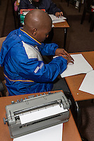 South Africa, Cape Town.  Blind Student Reading Braille.  A Perkins Brailler Printer is in the foreground.  Athlone School for the Blind.