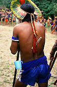 Altamira, Brazil. Xicrin Kayapo Indian from the back with blue plastic cup at his waist, comb hanging at his back. Altamira Gathering, 1989.