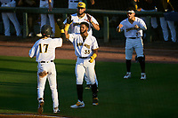 Bradenton Marauders Hudson Head (17) is greeted at home by Maikol Escotto (35), Adrian Florencio (45), and Francisco Acuna (3) after scoring a run during Game Two of the Low-A Southeast Championship Series against the Tampa Tarpons on September 22, 2021 at LECOM Park in Bradenton, Florida.  (Mike Janes/Four Seam Images)