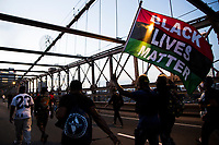 NEW YORK, USA - May 25: A man holds a Black Lives Matteren flag on the Brooklyn Bridge on the first anniversary of death on May 25, 2021 in New York City. The assassination of George Floyd in Minneapolis sparked a worldwide outcry and continued to push the Black Lives Matter movement through different cities in the United States and the world. (Photo by Pablo Monsalve / VIEWpress via Getty Images)