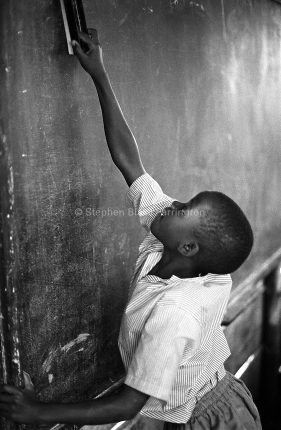 This young student cleans the blackboard in her primary three class at Rehaboth Integrated School. Most of the 130 plus children that attend this school are orphans due to HIV/AIDS. Uganda has an estimated 1.5 million people infected with HIV/AIDS and contains over 1 million orphans. Bugembe, Jinja District, Uganda, Africa. June 2004 © Stephen Blake Farrington