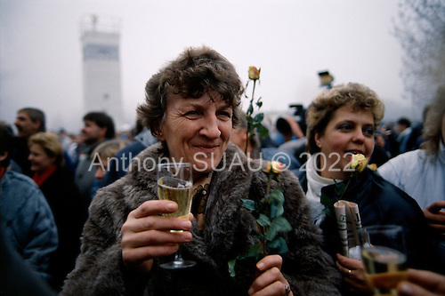 Lichterfelde, Berlin (West) and Teltow, Potsdam (East) crossing post, West Germany<br /> November 14, 1989  <br /> <br /> An unidentified woman holds up champagne at to celebrate as East Germans go to West Germany. Germans gathered as the wall is dismantled and the East German government lifts travel and emigration restrictions to the West on November 9, 1989.