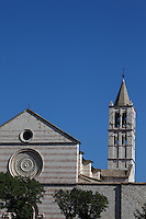 Assisi:  A classical view of the high part of the façade of the Santa Chiara church, with its typical partially rose-colored bricks. The bell-tower is on the top right, whereas on the bottom appear the green trees of the square in front of the church itself, among which one can distinguish the two small marble lions on the two main door sides.