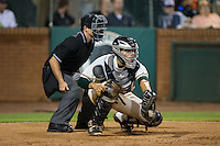 Greensboro Grasshoppers catcher Roy Morales (17) reaches for a pitch as home plate umpire Tom West looks on during the game against the Kannapolis Intimidators at NewBridge Bank Park on July 7, 2016 in Greensboro, North Carolina.  The Dash defeated the Pelicans 13-9.  (Brian Westerholt/Four Seam Images)