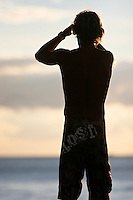 A young man looks out at the surf in Waikiki, Oahu, as the sun sets.