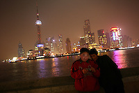 CHINA. Shanghai. Two tourists on the Bund with the famous PuDong skyline behind them. Shanghai is a sprawling metropolis or 15 million people situated in south-east China. It is regarded as the country's showcase in development and modernity in modern China. This rapid development and modernization, never seen before on such a scale has however spawned countless environmental and social problems. 2008.