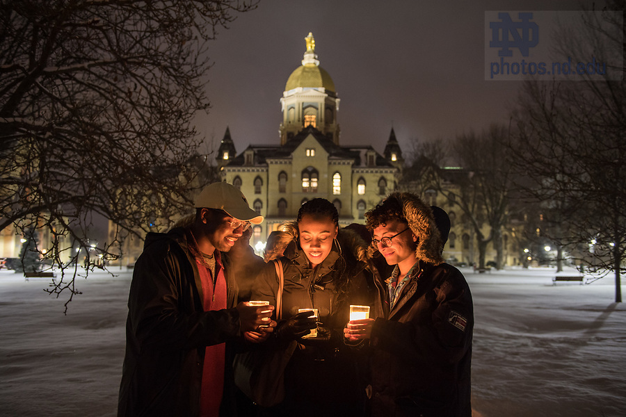 """January 15, 2018; Students and staff walk out of the Main Building after a midnight prayer service in honor of the Rev. Martin Luther King Jr. holiday. The event also marked the beginning of """"Walk the Walk"""" week, a series of events and observances to celebrate and reflect on diversity and inclusiveness. (Photo by Barbara Johnston/University of Notre Dame)"""