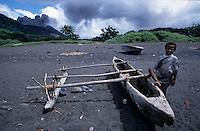 Melanesian boy standing next to a traditional wooden dugout canoe at Sulphur Bay near Ipekel Ipekel village on the island of Tanna, Vanuatu.
