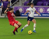 ORLANDO CITY, FL - FEBRUARY 18: Alex Morgan #13 dribbles the ball away from a sliding Vanessa Gilles #23 during a game between Canada and USWNT at Exploria stadium on February 18, 2021 in Orlando City, Florida.