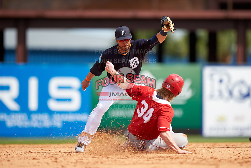 Detroit Tigers shortstop Mike Aviles (14) stretches for a throw as Mitch Reeves (34) slides into second base during an exhibition game against the Florida Southern Moccasins on February 29, 2016 at Joker Marchant Stadium in Lakeland, Florida.  Detroit defeated Florida Southern 7-2.  (Mike Janes/Four Seam Images)