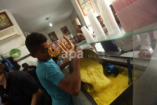 Palestinians buy ice-cream during hot weather in Gaza city on May 27, 2015. Hot weather hit Gaza Strip on Wednesday, and the temperature reached more than 39 degrees Celsius  (102 degree Fahrenheit) at noon, Gazans escape to the beach and out from their homes during heat wave and power outages. Photo by Ashraf Amra