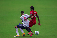 ORLANDO, FL - APRIL 24: Caio Alexandre #8 of Vancouver Whitecaps and Richie Laryea #22 of Toronto FC battle for the ball during a game between Vancouver Whitecaps and Toronto FC at Exploria Stadium on April 24, 2021 in Orlando, Florida.