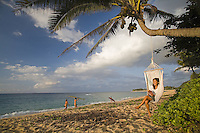 Young woman reading a book in a hammock with surfer girls in background, at Sunset Beach, North Shore of Oahu
